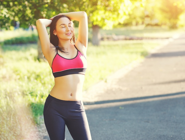 Porträt des schlanken jungen mädchens der fitness nach dem joggen in einem freiluftpark an einem hellen sonnigen tag. konzept des aktiven lebensstils und des outdoor-sports