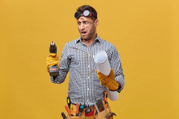 Porträt des schmutzigen reparaturmanns mit werkzeuggürtel, der blaupause hält und bohrmaschine, die es mit wut betrachtet, wie es schlecht arbeitet. handwerker drückt seine unzufriedenheit mit werkzeugen und instrumenten aus