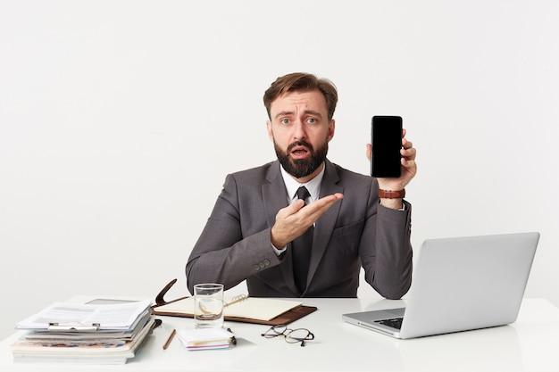Porträt des schockierten attraktiven bärtigen geschäftsmannes, manager, der am schreibtisch im büro sitzt und ungläubig in die kamera schaut, gekleidet in einen teuren anzug mit einer krawatte, auf sein smartphone zeigend.