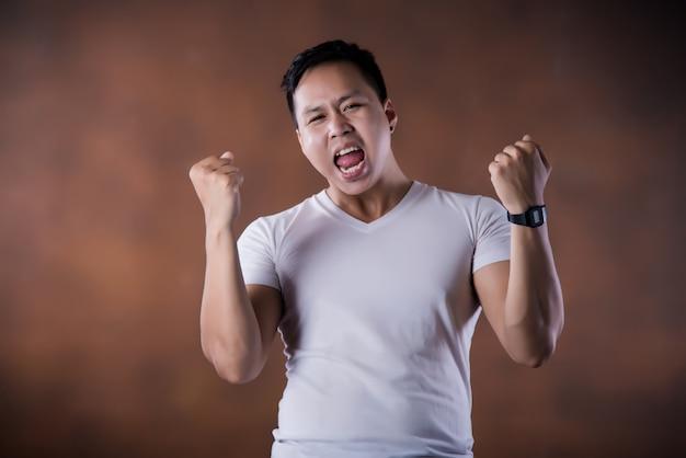 Porträt des schockierten fassungslosen überraschten jungen mannes augen und mund weit geöffnet
