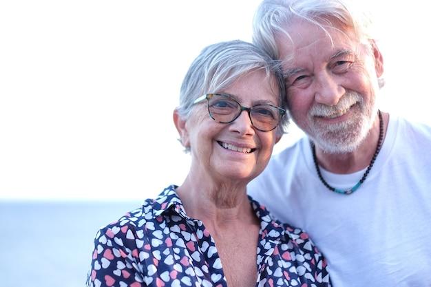 Porträt des schönen älteren paares, das im freien auf see bei sonnenuntergang lächelt. kaukasisches paar weißhaarig