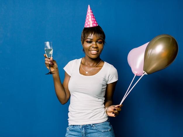 Porträt des schönen afrikanischen geburtstagsmädchens, das an der partei ruht. hübsches lächelndes afrikanisches mädchen, das glas mit champagner und luftballons hält, die auf blauem raum aufwerfen
