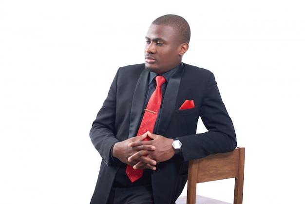Porträt des schönen afrikanischen geschäftsmannes, der elegante schwarze suite und rote krawatte trägt, die auf stuhl lehnt