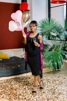 Porträt des schönen afrikanischen mädchens, das an der geburtstagsfeier mit luftballons und einem glas champagner in ihren händen ruht