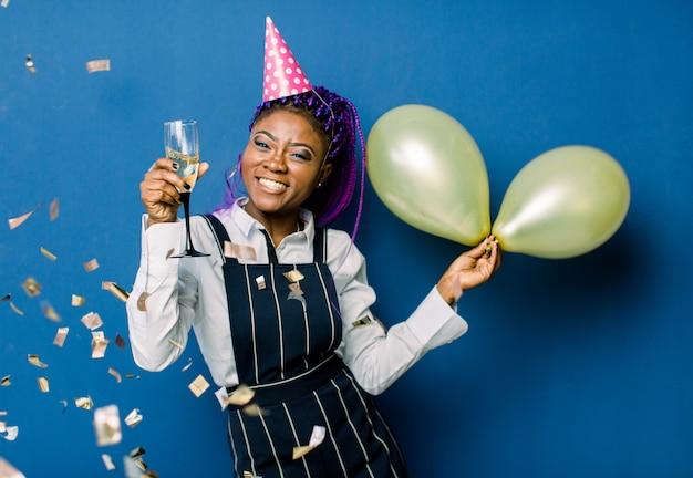 Porträt des schönen afrikanischen mädchens in der rosa partykappe, die luftballons und champagner hält, die an der partei ruhen. afrikanische frau, die spaß an der party mit konfetti auf blauem raum hat