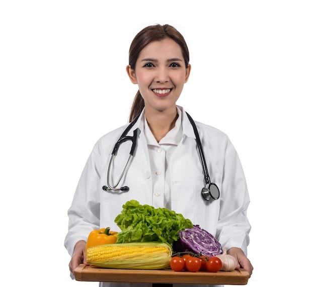 Porträt des schönen asiatischen jungen doktors, der das frischgemüse der mischung in der hölzernen platte hält