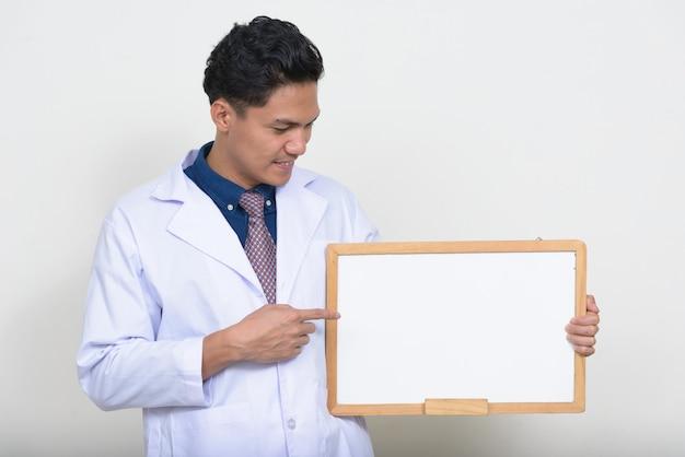Porträt des schönen asiatischen mannarztes, der weiße tafel hält
