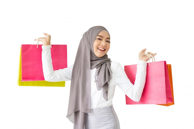 Porträt des schönen asiatischen moslemischen mädchens, das einkaufstaschen nah hochhält, lokalisiert auf weißer szene.
