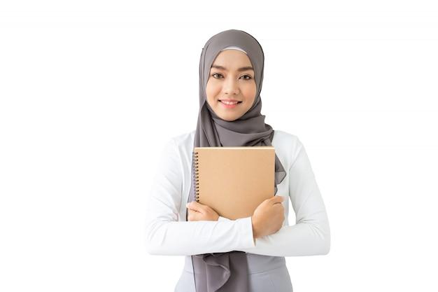 Porträt des schönen asiatischen moslemischen studenten, der ein buch und ein pencile, moslemisches studentendenken hält