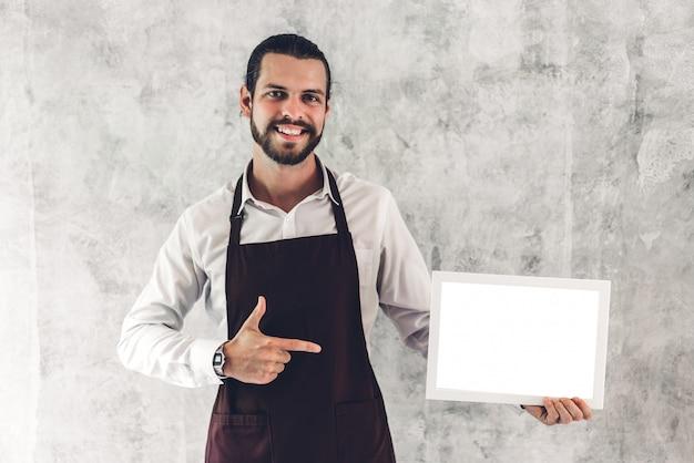 Porträt des schönen bärtigen barista-mann-kleinunternehmerin, der lächelnd und leeren hölzernen brettrahmen mit weißem rohling in einem café hält
