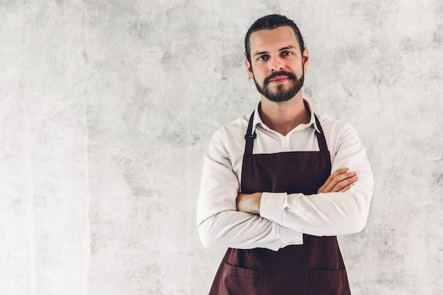 Porträt des schönen bärtigen barista-mannes kleinunternehmer, der auf wand lächelt