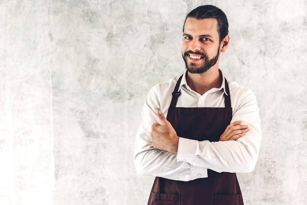 Porträt des schönen bärtigen barista-mannes kleinunternehmer, der auf wandwand lächelt