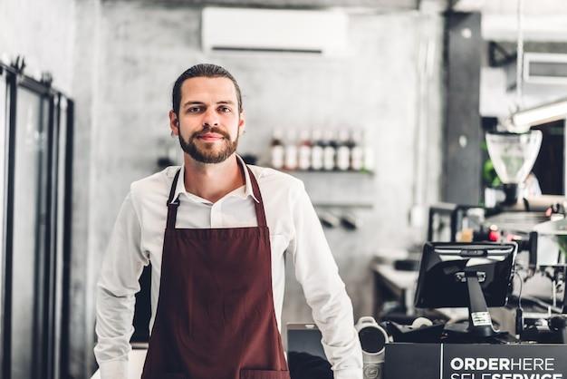 Porträt des schönen bärtigen barista-mannes kleinunternehmer, der hinter der thekenbar in einem café lächelt