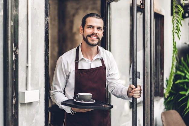 Porträt des schönen bärtigen barista-mannes kleinunternehmer, der lächelt und tasse kaffee im café oder im café hält. männlicher barista, der am café steht