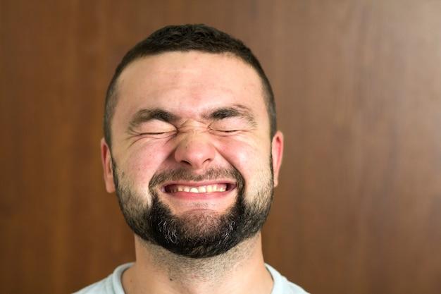 Porträt des schönen bärtigen schwarzhaarigen intelligenten modernen jungen mannes in gläsern mit kurzem haarschnitt und freundlichen schwarzen augen, die auf unscharfem hintergrund lächeln. jugend- und vertrauenskonzept.
