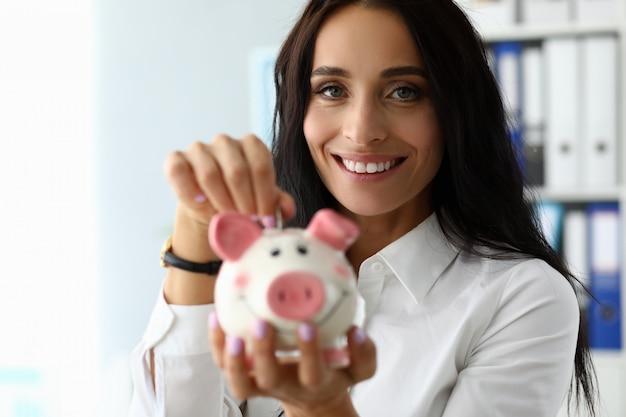 Porträt des schönen brunette gespeicherte münze in gebrauchtwagen einsetzend. wunderbare businesslady, die kamera mit freude und dem lächeln betrachtet. sparschwein-konzept