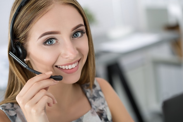 Porträt des schönen call-center-betreibers bei der arbeit. frau mit headset, die mit jemandem online spricht