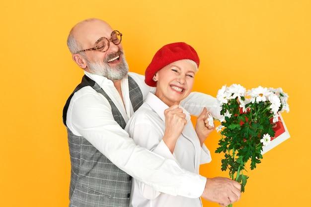 Porträt des schönen charismatischen älteren mannes mit kahlheit und grauem bart, der seine schöne frau in der roten baskenmütze umarmt