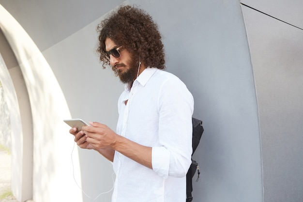Porträt des schönen dunkelhaarigen lockigen mannes mit sonnenbrille, die über graue außenwand aufwirft, tablette in händen hält und ernsthaft auf bildschirm schaut