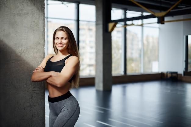 Porträt des schönen erwachsenen fitnesstrainers, der im fitnessstudio gestrandet ist. gesundes lebenskonzept.