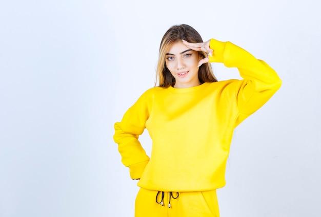 Porträt des schönen frauenmodells, das im gelben t-shirt steht und posiert