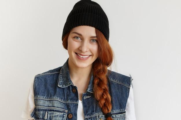 Porträt des schönen fröhlichen rothaarigen mädchens, das stilvolle schwarze wintermütze und ärmellose jeansjacke trägt