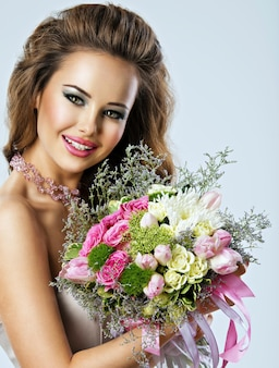Porträt des schönen glücklichen mädchens mit blumen in den händen. junge attraktive frau hält den blumenstrauß der frühlingsblumen