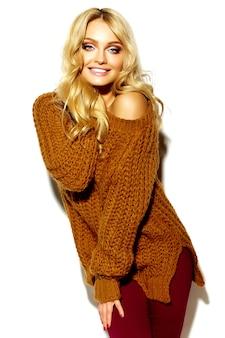 Porträt des schönen glücklichen niedlichen lächelnden blonden frauenmädchens in der warmen winterkleidung des lässigen hipsters im braunen pullover