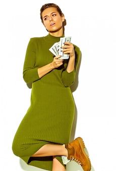 Porträt des schönen glücklichen niedlichen lächelnden brünetten frauenmädchens in der lässigen grünen hipster-sommerkleidung lokalisiert auf weißem halten dollar-banknote in händen