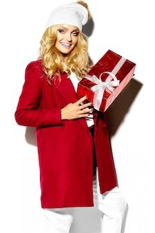 Porträt des schönen glücklichen süßen lächelnden blonden frauenmädchens, das in ihren händen große weihnachtsgeschenkbox in lässiger roter hipster-winterkleidung hält