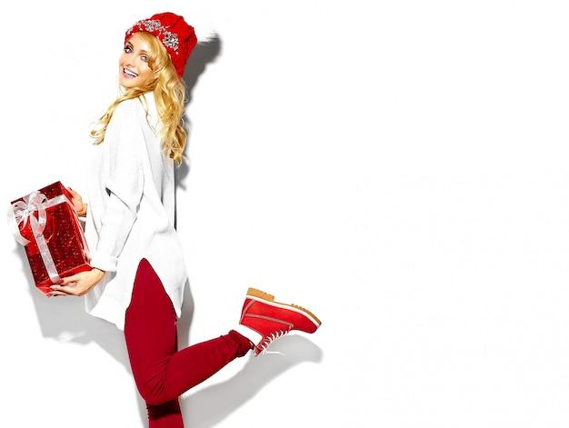 Porträt des schönen glücklichen süßen lächelnden blonden frauenmädchens, das in ihren händen große weihnachtsgeschenkbox in lässiger roter hipster-winterkleidung, im weißen warmen pullover auf einem bein stehend hält