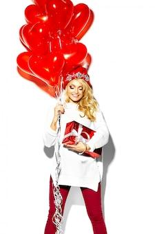 Porträt des schönen glücklichen süßen lächelnden blonden frauenmädchens, das in ihren händen große weihnachtsgeschenkbox und herzballons in lässiger roter hipster-winterkleidung, im weißen warmen pullover hält
