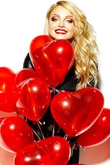 Porträt des schönen glücklichen süßen lächelnden blonden frauenmädchens, das in ihren händen rote herzballons in lässigen schwarzen hipster-kleidern hält