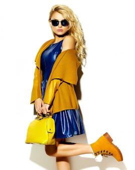 Porträt des schönen glücklichen süßen lächelnden blonden frauenmädchens in der warmen winterpulloverkleidung des lässigen hipsters, mit der gelben handtasche in der sonnenbrille