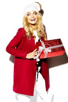 Porträt des schönen glücklichen süßen lächelnden überraschten blonden frauenmädchens, das in ihren händen große weihnachtsgeschenkbox in lässiger roter hipster-winterkleidung hält