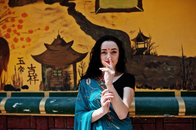 Porträt des schönen indischen brumette mädchen- oder hindischen frauenmodells gegen japanische grafiti wand.