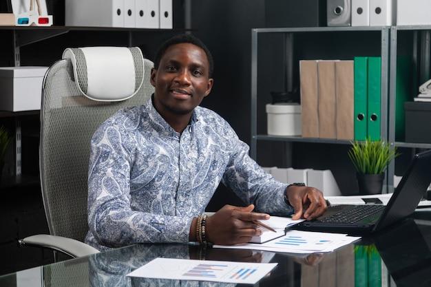 Porträt des schönen jungen afroamerikanergeschäftsmannes, der mit dokumenten und laptop im büro arbeitet