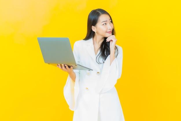 Porträt des schönen jungen asiatischen frauenlächelns mit computerlaptop auf gelber wand