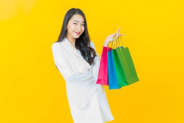 Porträt des schönen jungen asiatischen frauenlächelns mit einkaufstüten auf gelber wand