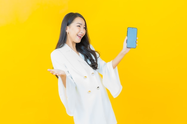 Porträt des schönen jungen asiatischen frauenlächelns mit intelligentem handy auf gelber wand