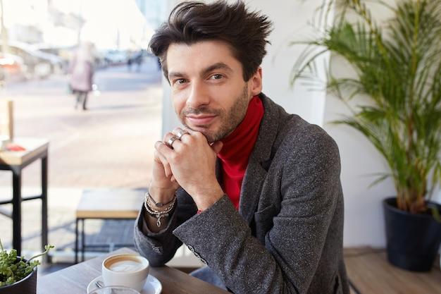 Porträt des schönen jungen bärtigen brünetten mannes, der positiv in die kamera mit charmantem lächeln schaut und seinen kopf auf erhobene hände stützt, während er im stadtcafé sitzt