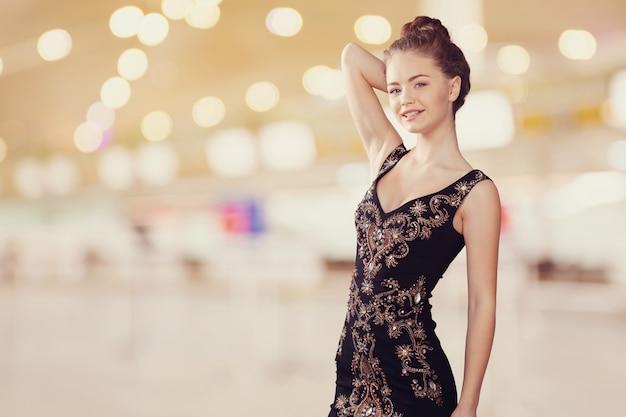Porträt des schönen jungen blonden mädchens im schwarzen kleid