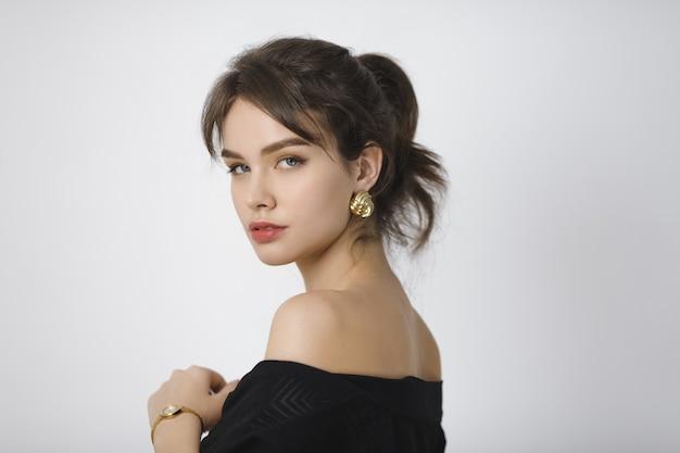Porträt des schönen jungen brünetten mädchens im schwarzen kleid