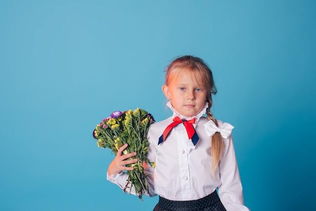 Porträt des schönen jungen erstklässlers. erstklässlerin im studio mit blumen