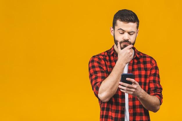 Porträt des schönen jungen erwachsenen mit verträumtem blick, denkend, während smartphone gehalten, lokalisiert über gelbe wand. sohn versucht, eine nachricht für seinen vater zu erfinden und erklärt, warum er mit dem auto gefahren ist.