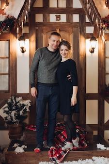 Porträt des schönen jungen erwachsenen paares, das sich auf holzbank im weihnachtsinnenraum kuschelt