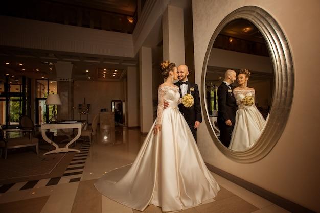 Porträt des schönen jungen gerade verheirateten paares, das vor einem großen spiegel aufwirft