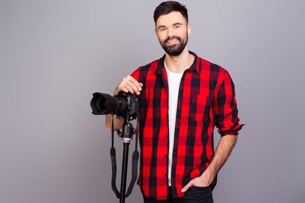 Porträt des schönen jungen kameramanns, der im studio mit kamera steht