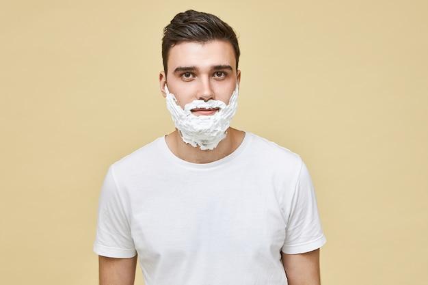 Porträt des schönen jungen kaukasischen brünetten mannes, der isoliert mit weißem rasierschaum posiert, der auf seinem gesicht angewendet wird, haut für die rasur vorbereitend aufwirft. morgenroutine, männlichkeit, schönheit und pflegekonzept