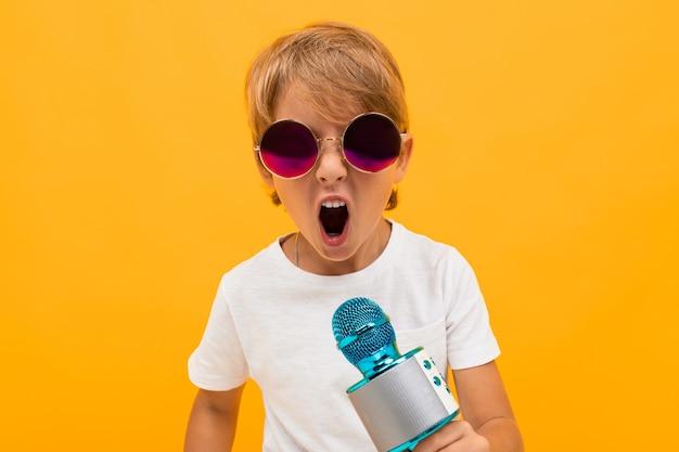 Porträt des schönen jungen kaukasischen jungen im weißen t-shirt und in der grauen hose lächelt und singt lieder